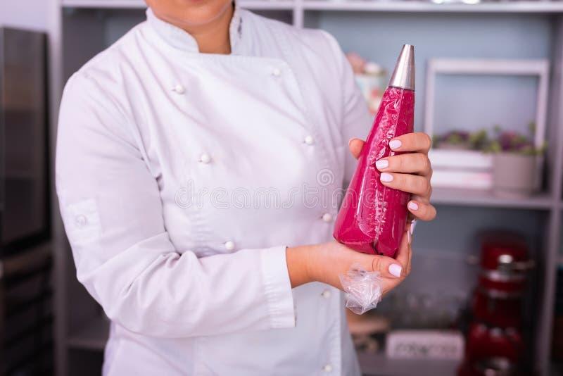 Cocinero de sexo femenino que sostiene el bolso de los pasteles con el merengue rosado que cocina el postre fotos de archivo libres de regalías