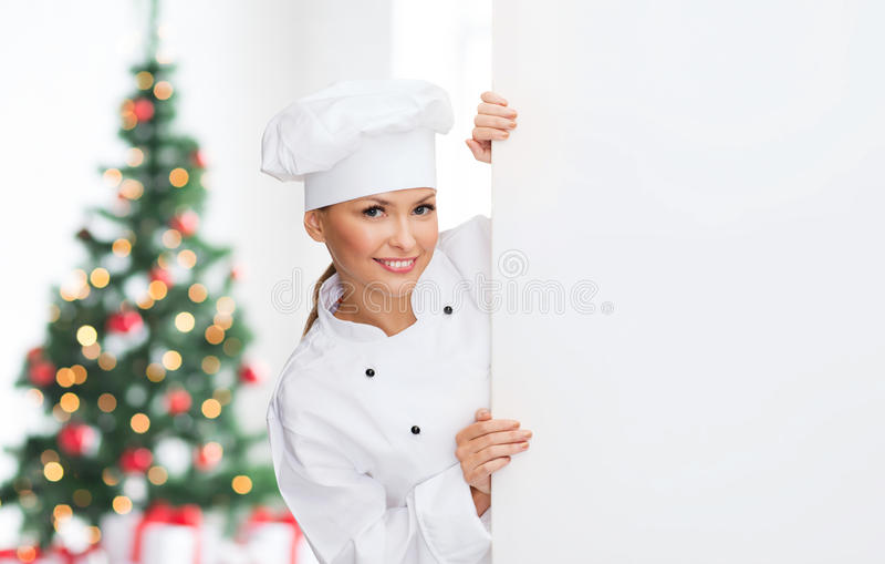 Cocinero de sexo femenino sonriente con el tablero en blanco blanco fotografía de archivo