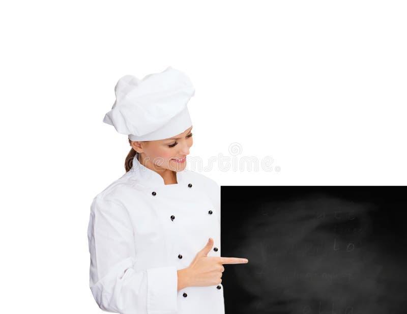 Cocinero de sexo femenino sonriente con el tablero en blanco blanco fotos de archivo