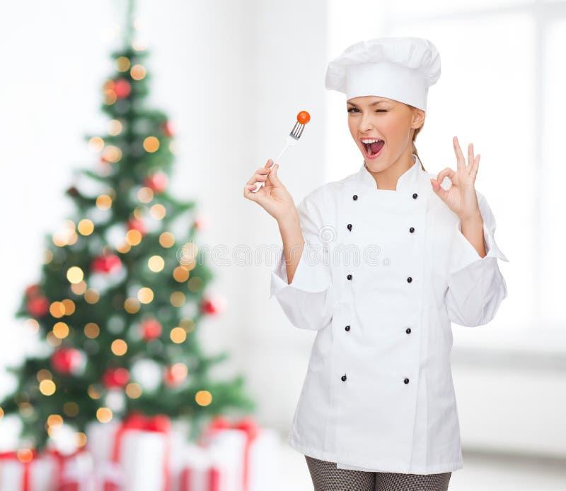 Cocinero de sexo femenino sonriente con la bifurcación que muestra la muestra aceptable foto de archivo libre de regalías