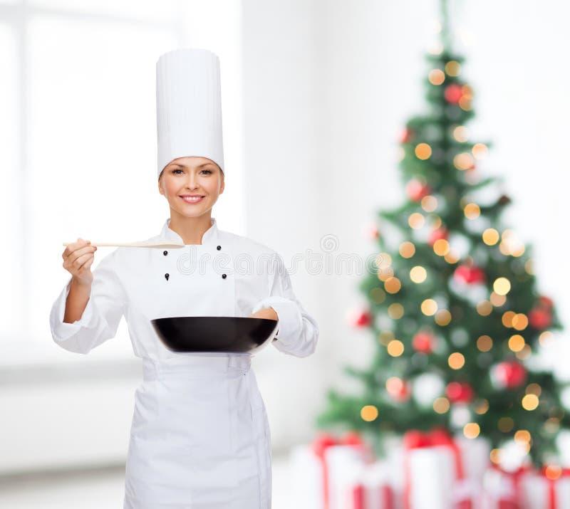 Cocinero de sexo femenino sonriente con la cacerola y la cuchara imagen de archivo libre de regalías