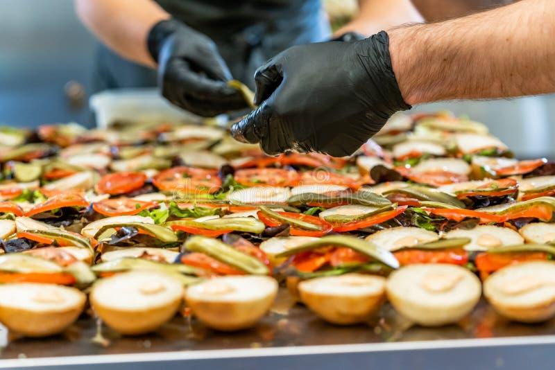 Cocinero de sexo femenino y de sexo masculino Putting Ingredients de hamburguesas en una extensión cortada del pan en una tabla e fotos de archivo libres de regalías