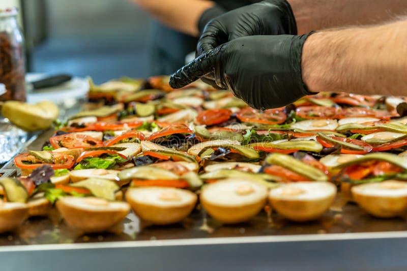 Cocinero de sexo femenino y de sexo masculino Putting Ingredients de hamburguesas en una extensión cortada del pan en una tabla e foto de archivo