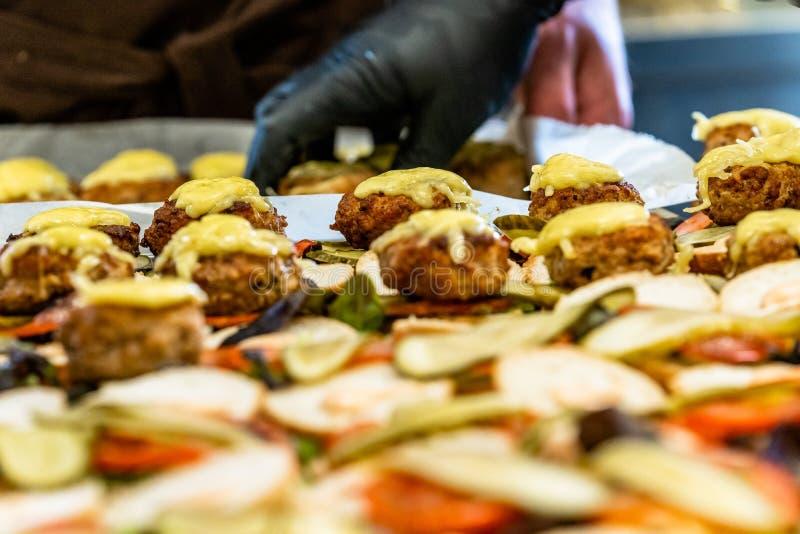 Cocinero de sexo femenino y de sexo masculino Putting Ingredients de hamburguesas en una extensión cortada del pan en una tabla e fotografía de archivo