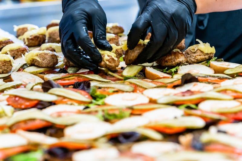 Cocinero de sexo femenino y de sexo masculino Putting Ingredients de hamburguesas en una extensión cortada del pan en una tabla e imagen de archivo