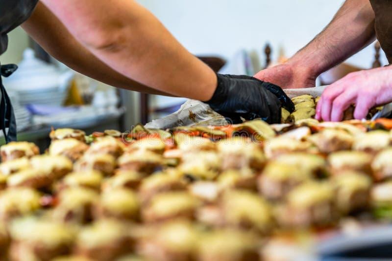 Cocinero de sexo femenino y de sexo masculino Putting Ingredients de hamburguesas en una extensión cortada del pan en una tabla e imagen de archivo libre de regalías