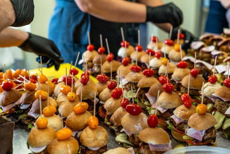 Cocinero de sexo femenino y de sexo masculino Putting Ingredients de hamburguesas en una extensión cortada del pan en una tabla e foto de archivo libre de regalías