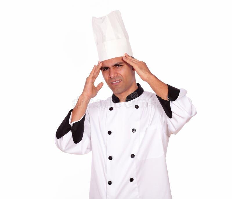 Cocinero de sexo masculino cansado que se coloca con dolor de cabeza fotografía de archivo libre de regalías