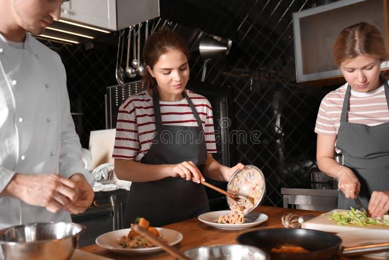 Cocinero de sexo masculino con las mujeres jovenes que preparan la ensalada durante clases de cocina en cocina del restaurante imágenes de archivo libres de regalías