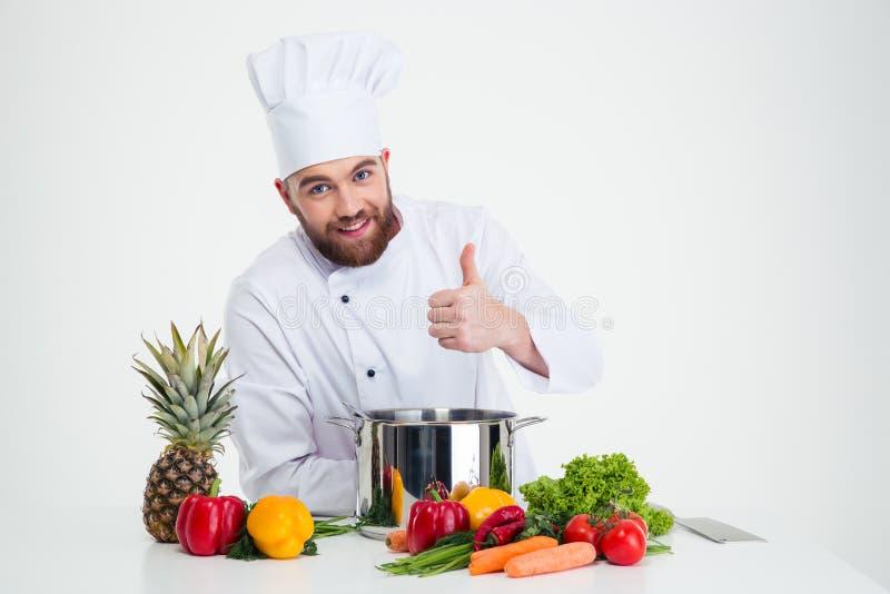 Cocinero de sexo masculino del cocinero que prepara la comida y que muestra el pulgar para arriba foto de archivo libre de regalías