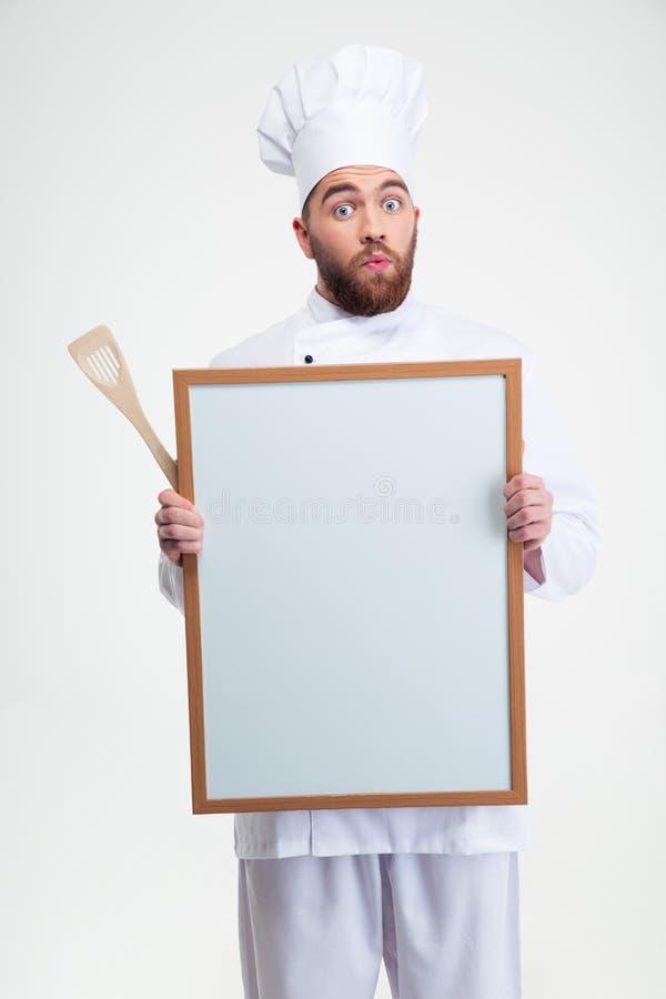 Cocinero de sexo masculino divertido del cocinero que lleva a cabo al tablero en blanco fotos de archivo