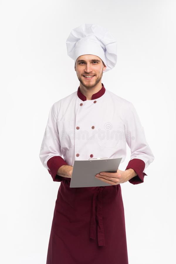 Cocinero de sexo masculino joven alegre que escribe en un tablero contra el fondo blanco imagen de archivo