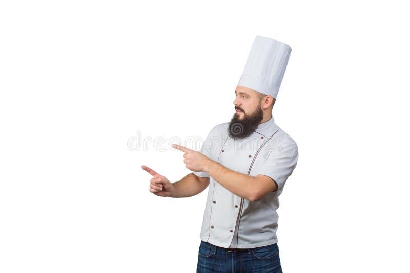 Cocinero de sexo masculino joven encantador del cocinero que señala los fingeres en uniforme del blanco sobre el fondo blanco foto de archivo libre de regalías