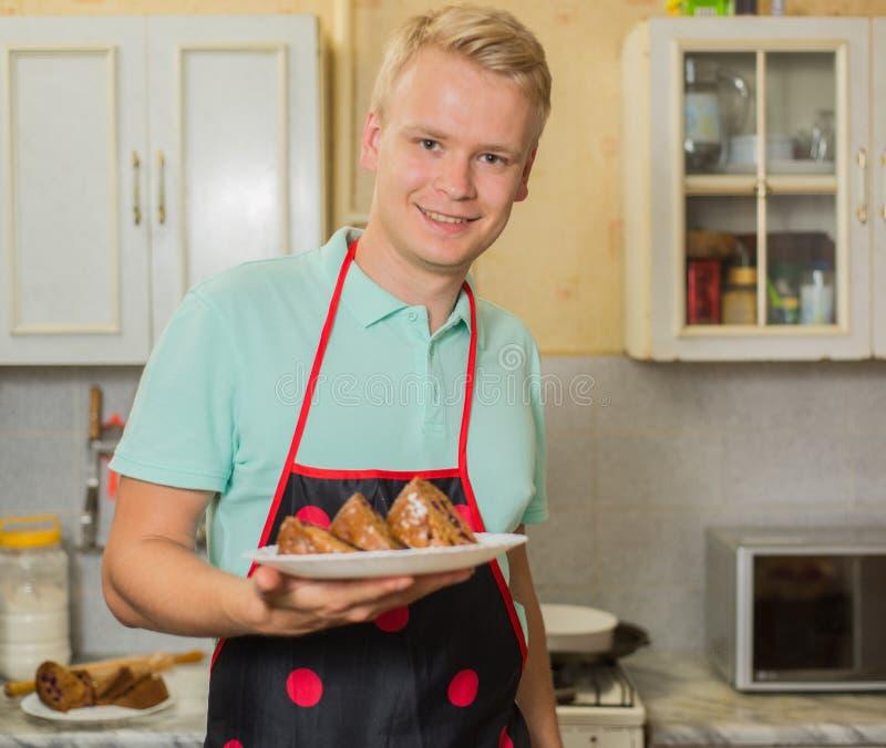 Cocinero de sexo masculino joven sonriente en un delantal que sostiene una torta, colocándose en la cocina casera fotos de archivo