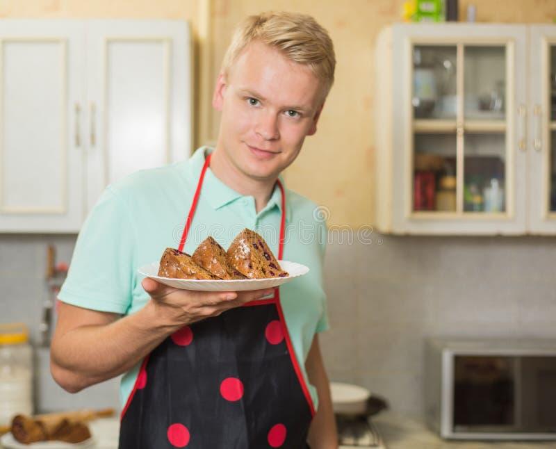 Cocinero de sexo masculino joven sonriente en un delantal que sostiene una torta, colocándose en la cocina casera foto de archivo