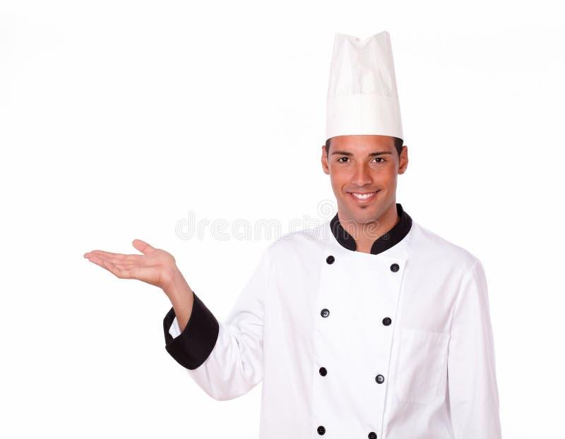 Cocinero de sexo masculino profesional que soporta su palma derecha foto de archivo