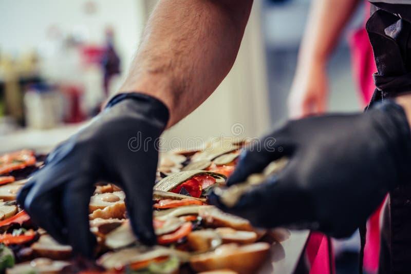 Cocinero de sexo masculino Putting Ingredients de hamburguesas en una extensión cortada del pan en una tabla en guantes negros fotografía de archivo