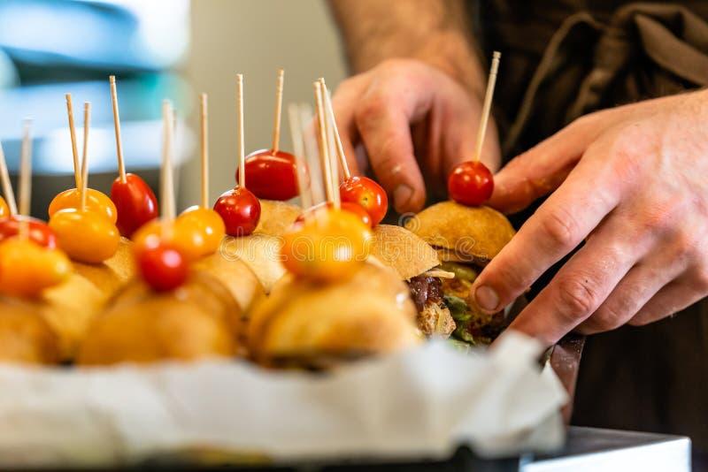 Cocinero de sexo masculino Putting Ingredients de hamburguesas en una extensión cortada del pan en una tabla en guantes negros imagen de archivo