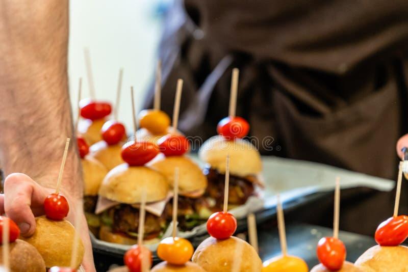 Cocinero de sexo masculino Putting Ingredients de hamburguesas en una extensión cortada del pan en una tabla en guantes negros imágenes de archivo libres de regalías