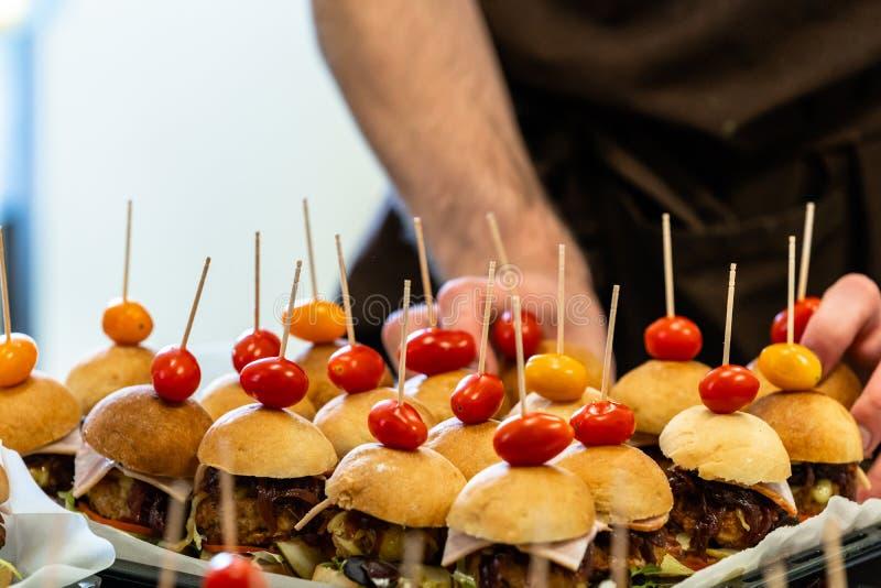 Cocinero de sexo masculino Putting Ingredients de hamburguesas en una extensión cortada del pan en una tabla en guantes negros imagen de archivo libre de regalías