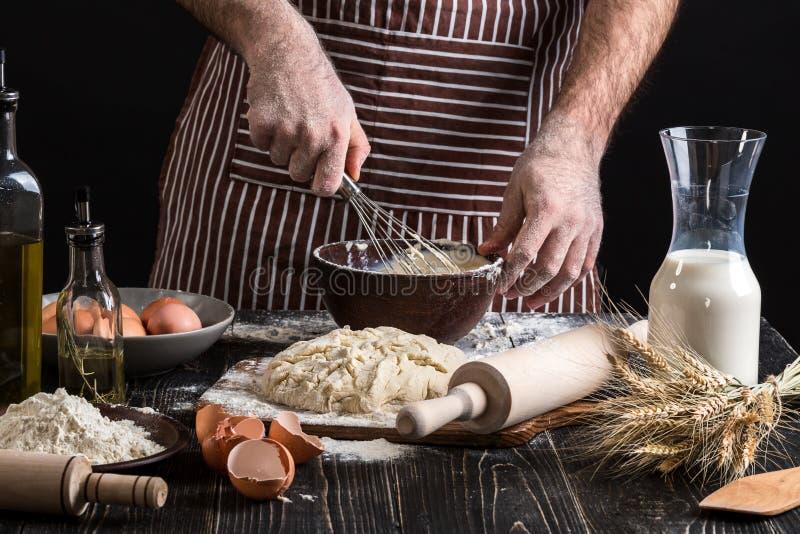 Cocinero de sexo masculino que azota los huevos en la panadería en la tabla de madera Ingredientes para cocinar productos o la pa imágenes de archivo libres de regalías