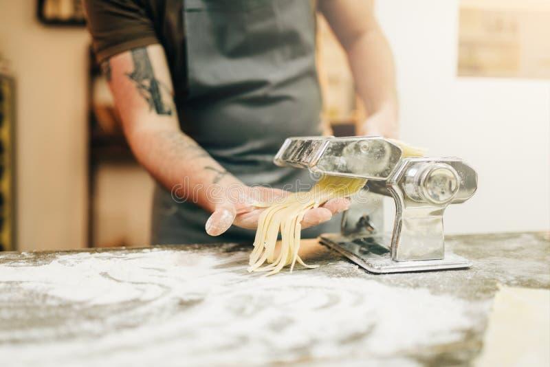 Cocinero de sexo masculino que cocina el fettuccine en máquina de las pastas fotos de archivo