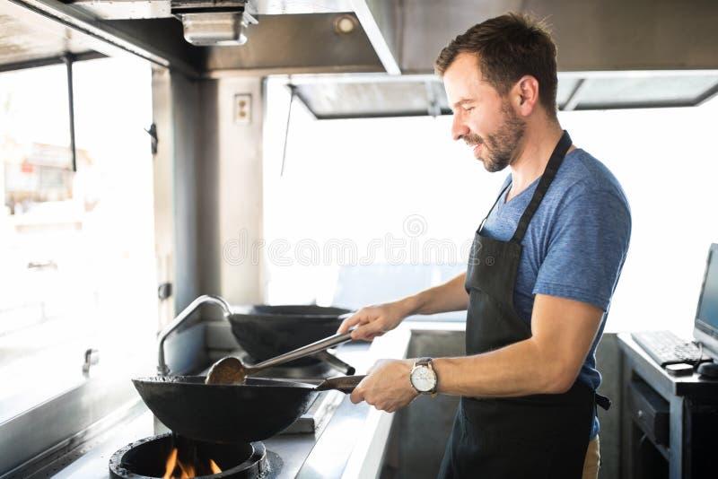 Cocinero de sexo masculino que cocina en un camión de la comida imágenes de archivo libres de regalías