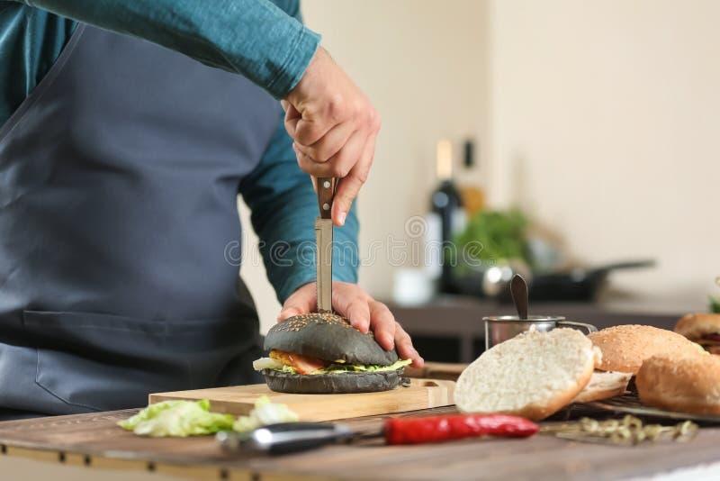 Cocinero de sexo masculino que prepara la hamburguesa en cocina imagen de archivo
