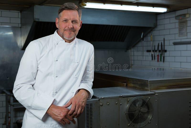 Cocinero de sexo masculino que se coloca en cocina comercial foto de archivo