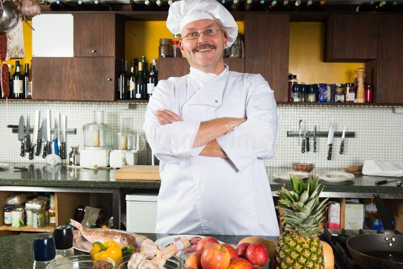 Cocinero de sexo masculino que se coloca en su cocina foto de archivo
