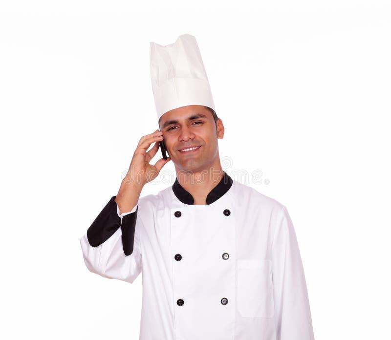 Cocinero de sexo masculino sonriente que conversa en el teléfono móvil imagen de archivo libre de regalías