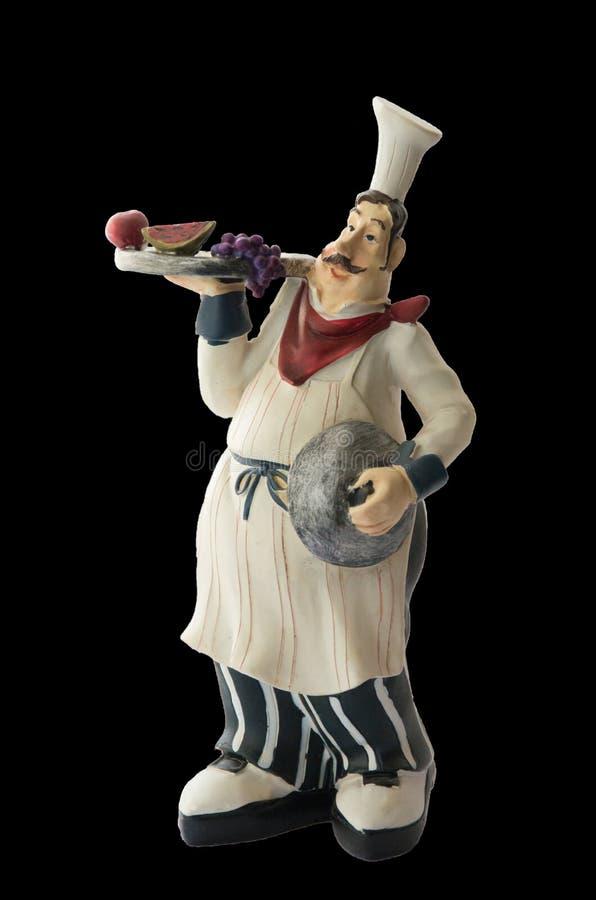 Cocinero decorativo del juguete con un espaciamiento en sus manos recuerdo Aislado en fondo negro imagen de archivo