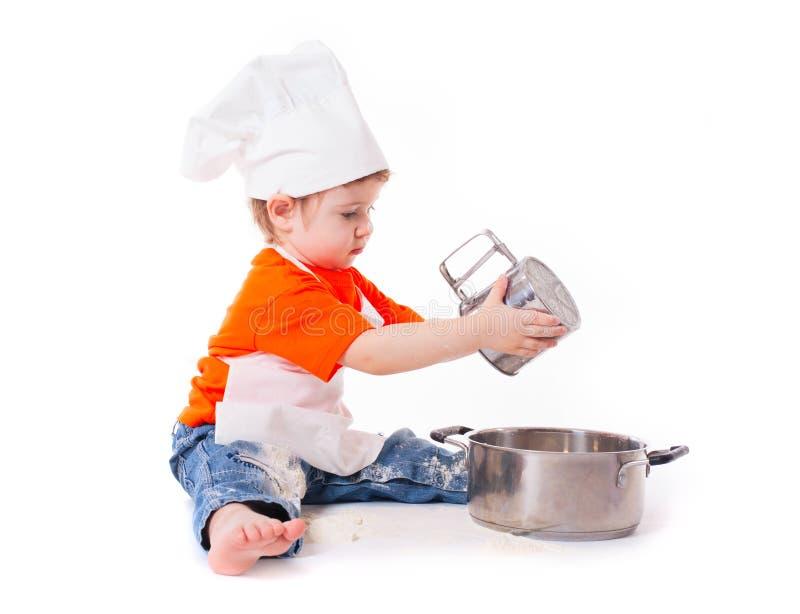 Cocinero del bebé que tamiza la harina aislada en el fondo blanco imagenes de archivo