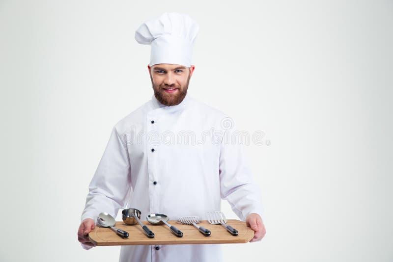 Cocinero del cocinero que lleva a cabo a la tajadera de madera con las cucharas fotos de archivo