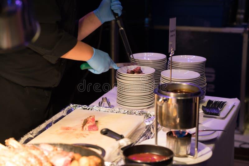 Cocinero del hotel que corta la costilla de repuesto asada a la parrilla de la carne de vaca con el cuchillo y las FO largos foto de archivo libre de regalías