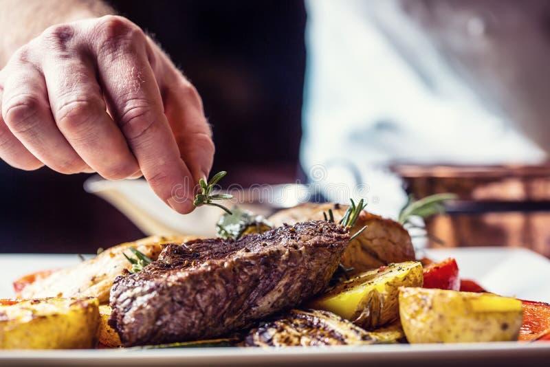 Cocinero en cocina del hotel o del restaurante que cocina solamente las manos Filete de carne de vaca preparado con la decoración foto de archivo