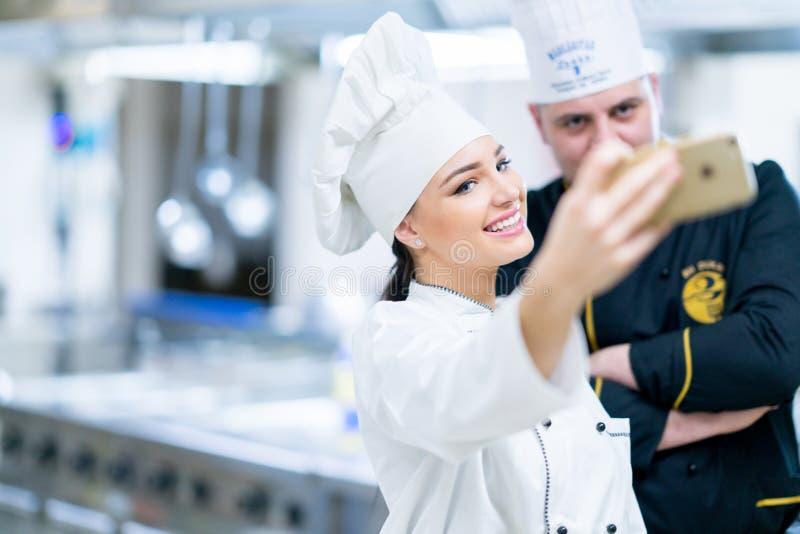 Cocinero en cocina y su ayudante joven que toma el selfie foto de archivo libre de regalías