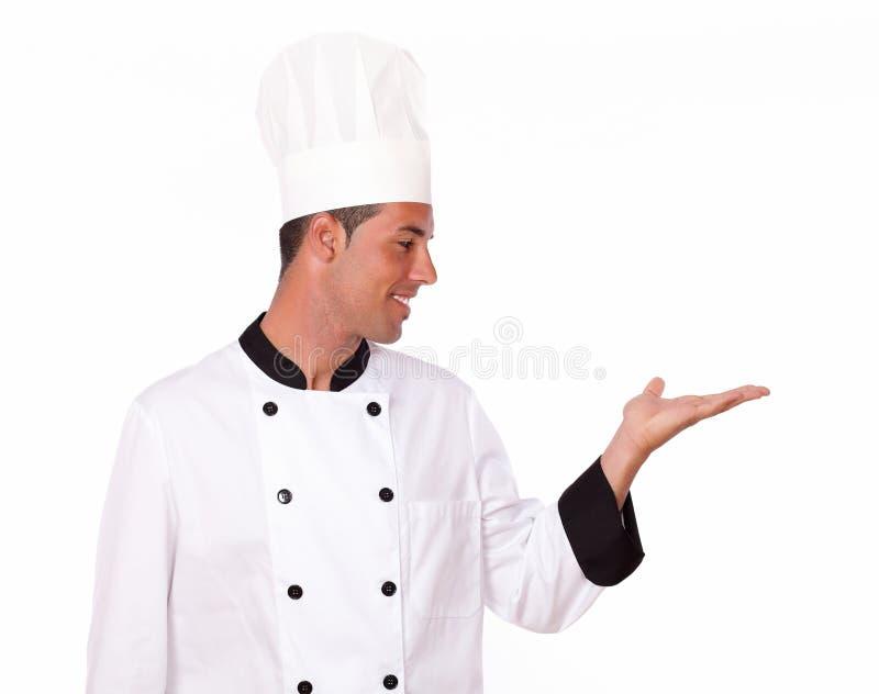 Cocinero encantador que soporta su palma izquierda imagenes de archivo