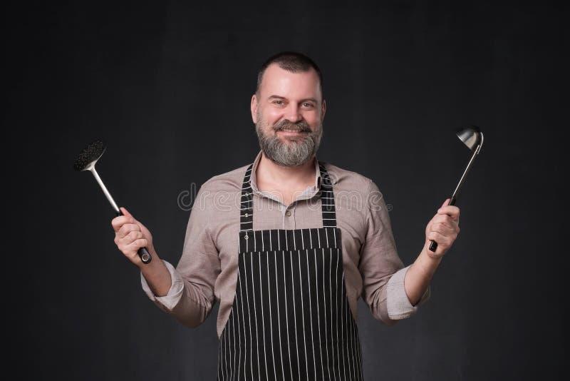 Cocinero europeo maduro con la barba que lleva a cabo una situaci?n de la cuchar?n en la pared negra del estudio imagen de archivo