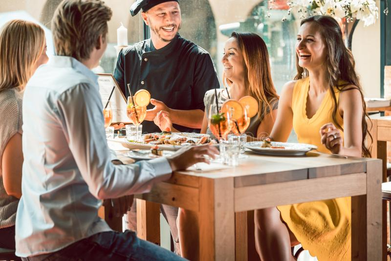 Cocinero experimentado felicitado por cuatro personas en un restaurante de moda fotografía de archivo libre de regalías