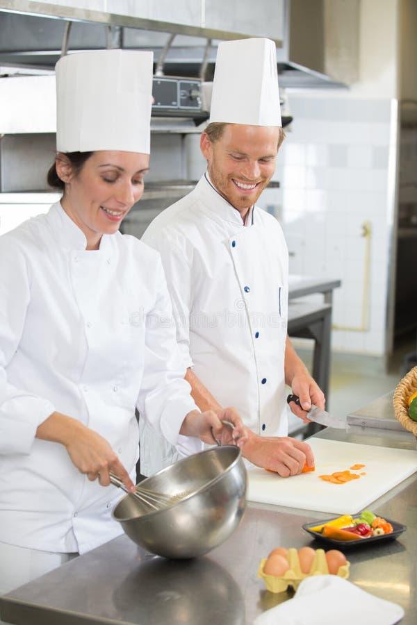 Cocinero feliz con el ayudante femenino sonriente hermoso en la cocina imagen de archivo