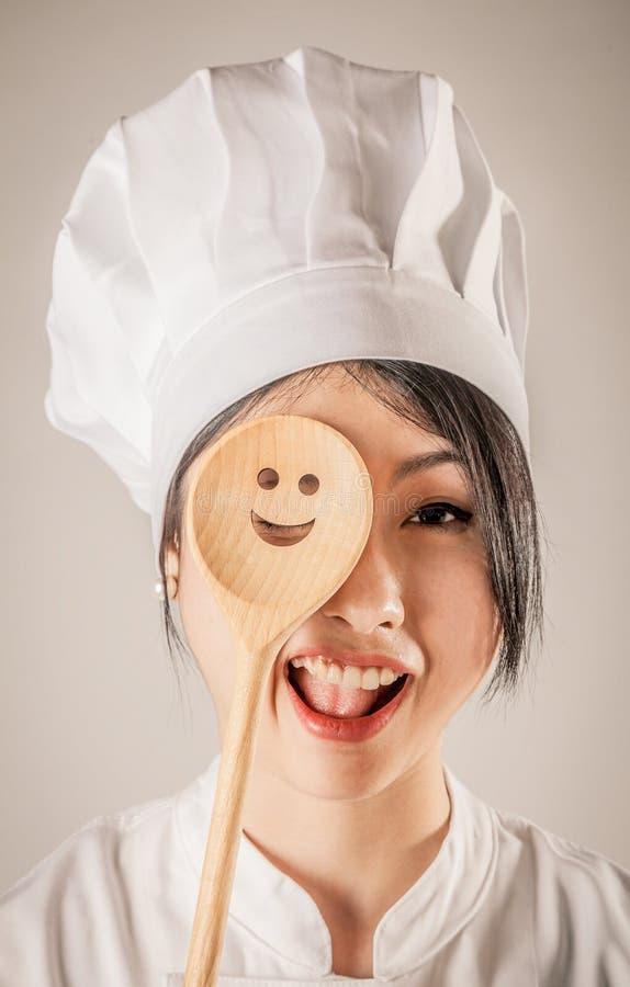 Cocinero feliz Covering One Eye con la cucharón de madera foto de archivo