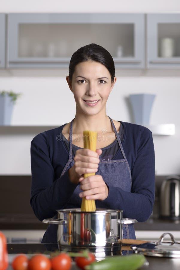 Cocinero feliz de los jóvenes que prepara los espaguetis italianos fotografía de archivo libre de regalías