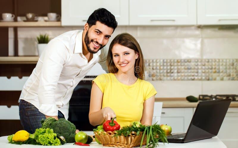 Cocinero feliz de los pares con el ordenador portátil foto de archivo