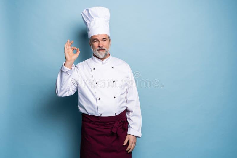 Cocinero feliz profesional maduro del hombre que muestra la muestra sabrosa de la autorización aislada en fondo azul claro fotografía de archivo libre de regalías