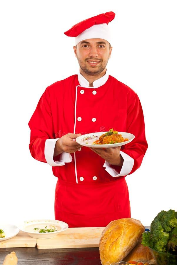 Cocinero feliz que muestra la comida en la placa fotografía de archivo