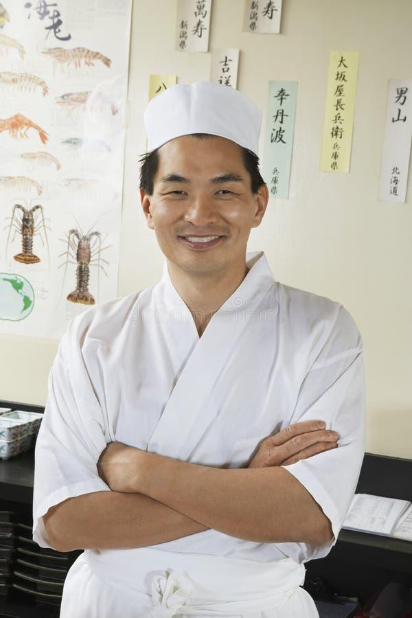 Cocinero feliz Standing In Restaurant foto de archivo libre de regalías