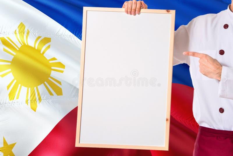 Cocinero filipino que lleva a cabo el menú en blanco del whiteboard en fondo de la bandera de Filipinas Cocine el uniforme que ll imagenes de archivo