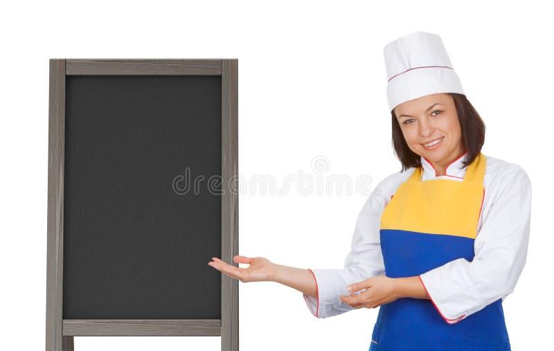 Cocinero hermoso de la mujer joven cerca de la pizarra de madera en blanco del menú hacia fuera fotos de archivo libres de regalías