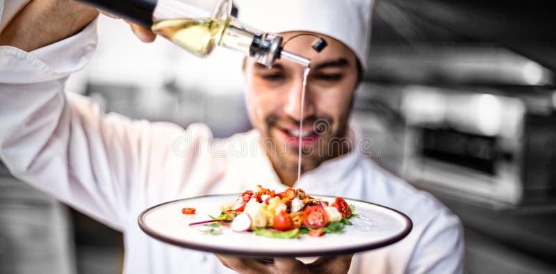 Cocinero hermoso que vierte el aceite de oliva en comida fotografía de archivo libre de regalías
